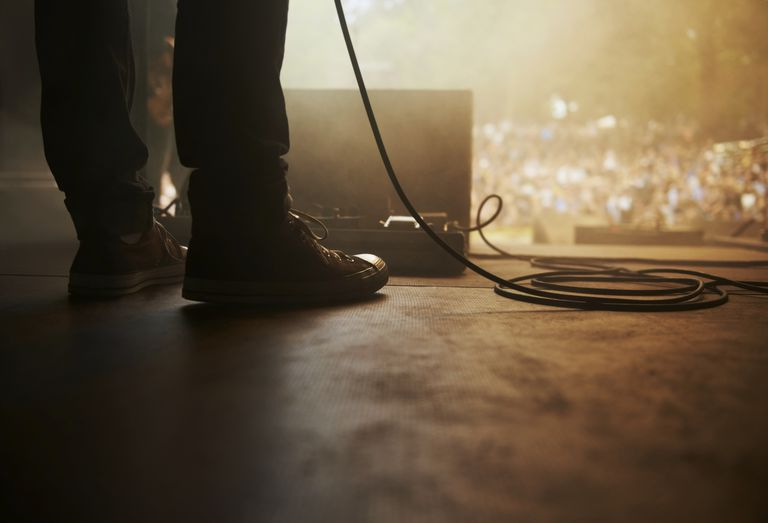 band member's feet on stage with amp and cord
