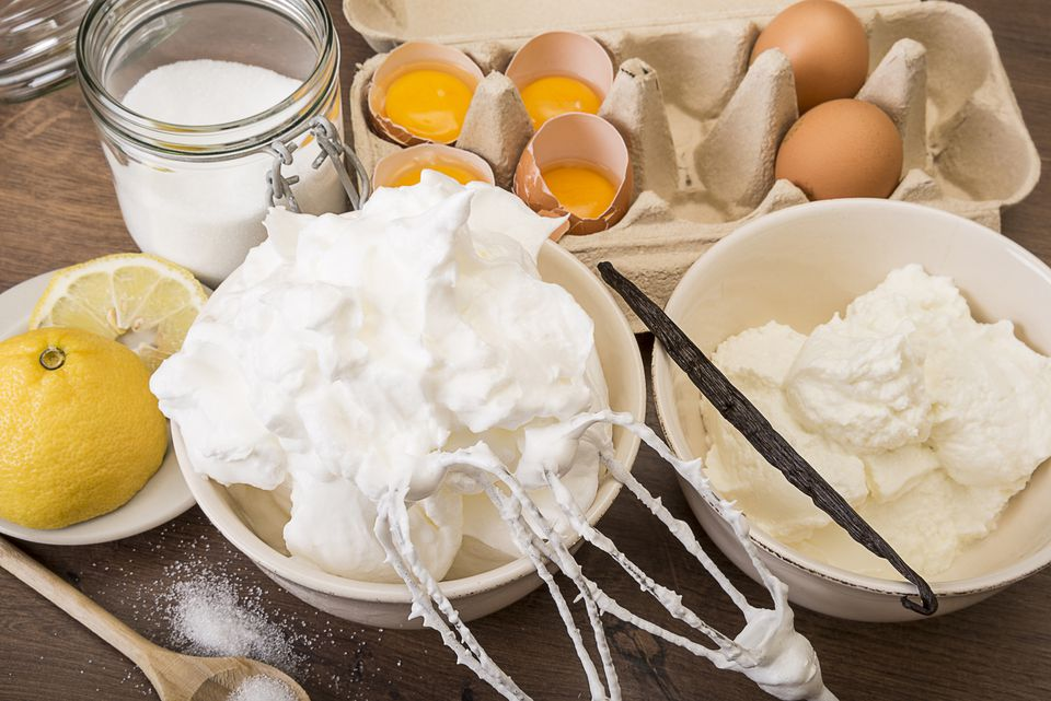 Bowl of beaten egg white and other baking ingredients of meringues on wooden table