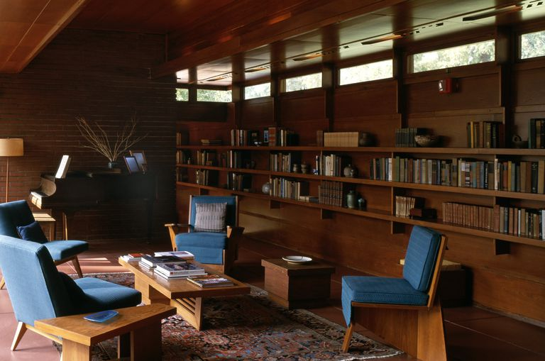 Mid-century modern living room, blue chairs, built-in bookcases along wall under horizontal windows along the top of the natural wood wall