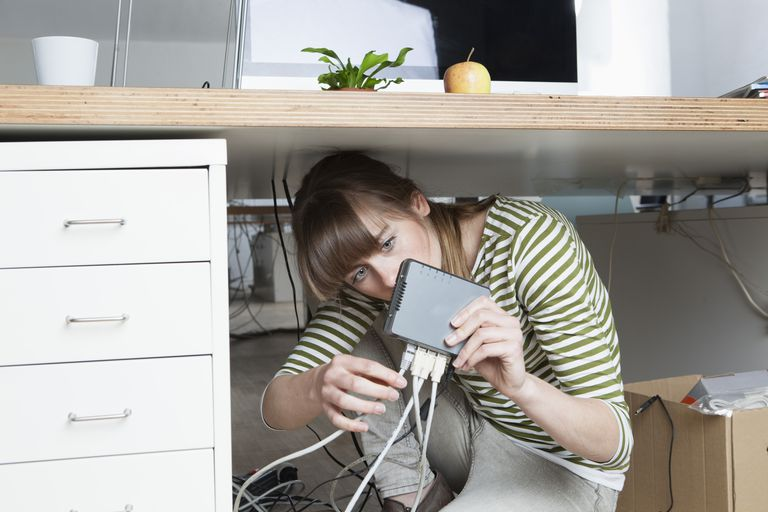 Young woman crouching under a desk connecting a modem in an office