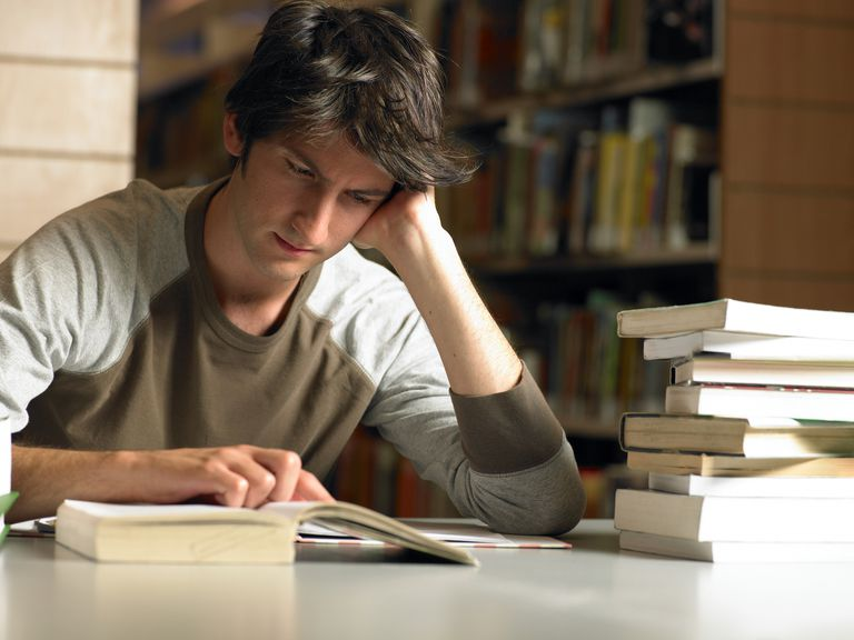 Young man reading in library, close-up