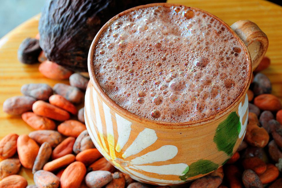 Frothy Mexican hot chocolate with cacao nibs and a cacao pod.