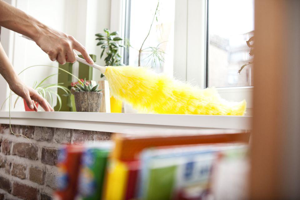 Woman dusting window sill