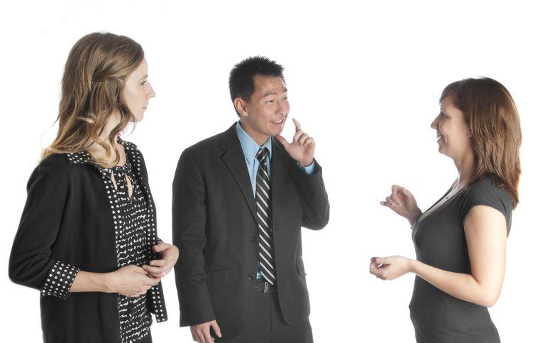 Interpreter watching two people converse in ASL