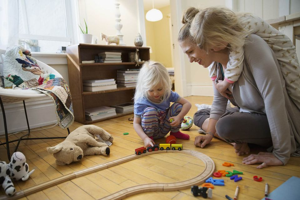 A picture of a family playing trains together