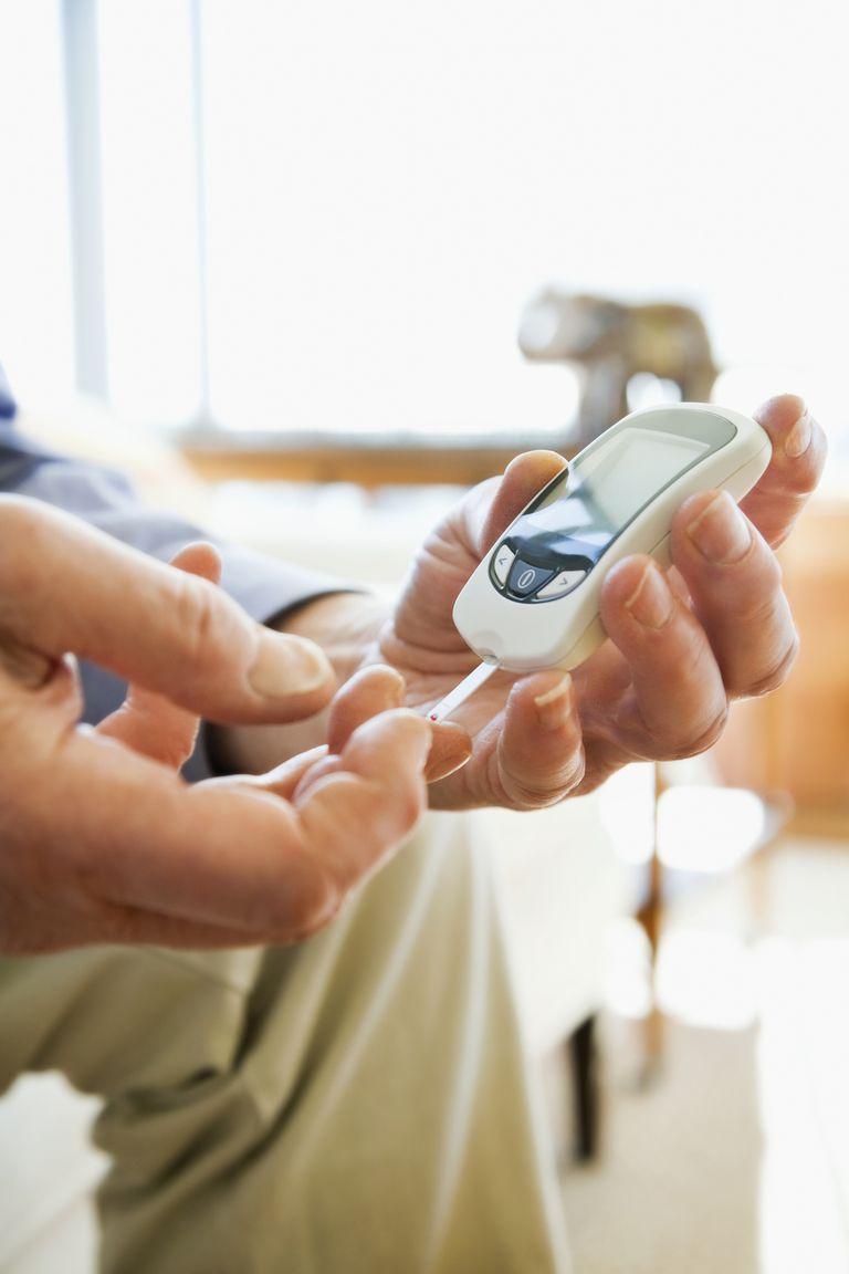 Mature man diabetic testing himself at home