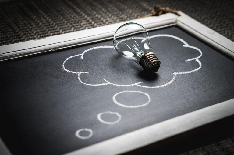 a light bulb placed in a chalk drawn idea bubble