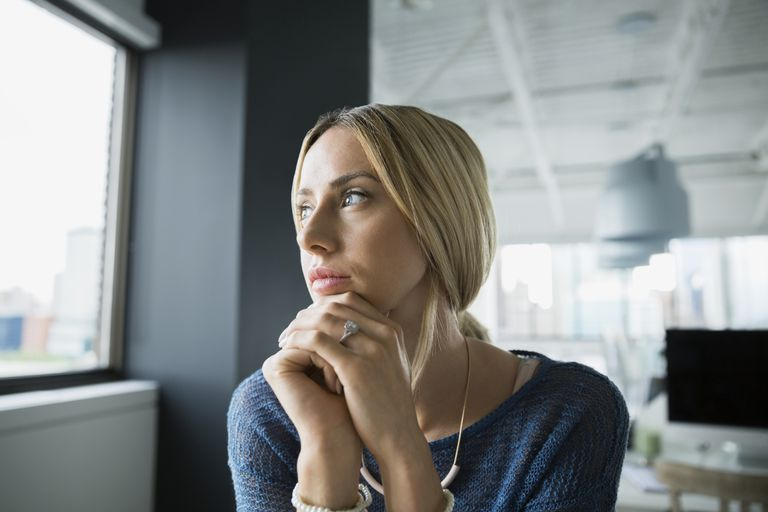 Pensive woman looking out office window