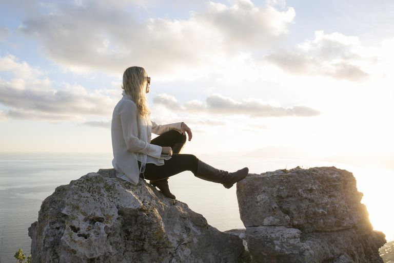 Woman sits on rock with tablet, looks across sea