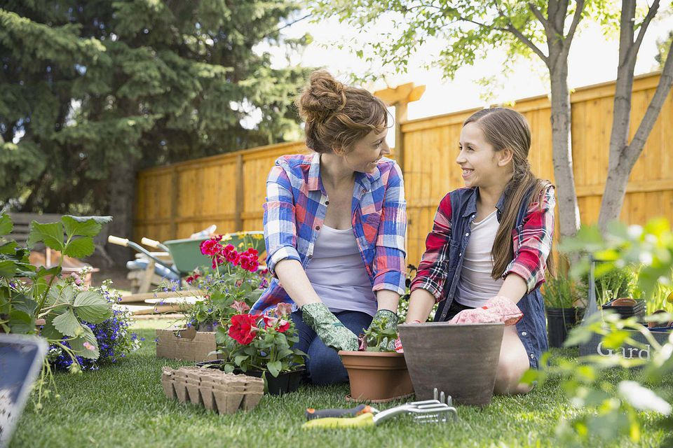 A picture of a mother and daughter planting flowers