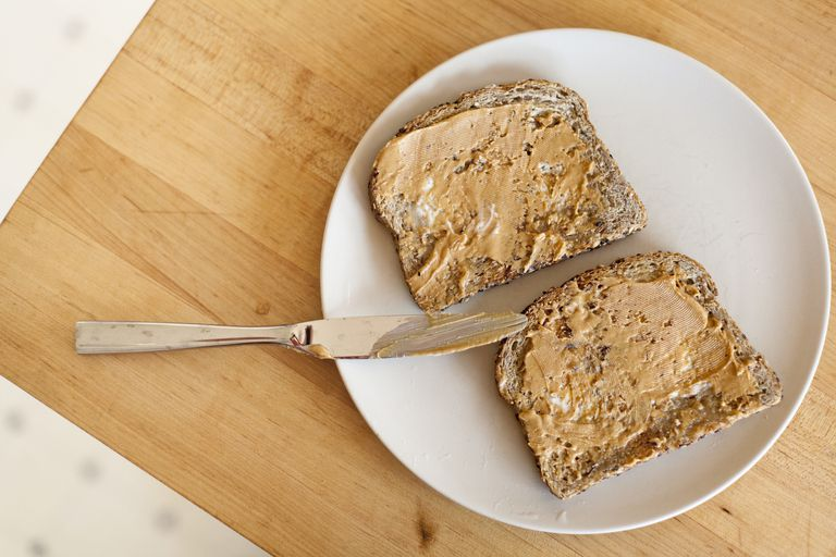 A top down view of peanut butter on toast on a plate with a knife on a kitchen table in a home.
