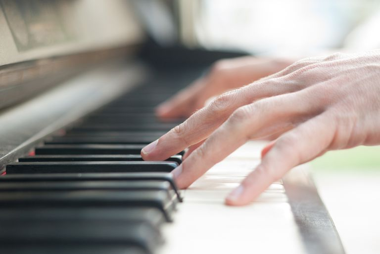 close-up of hands on piano