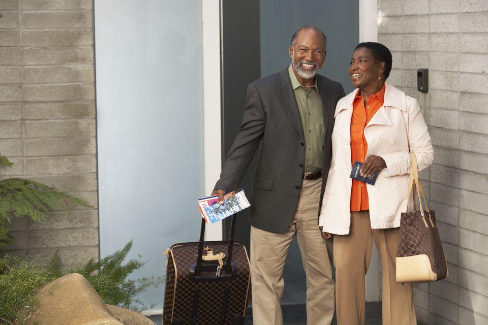 Senior couple with wheeled suitcase