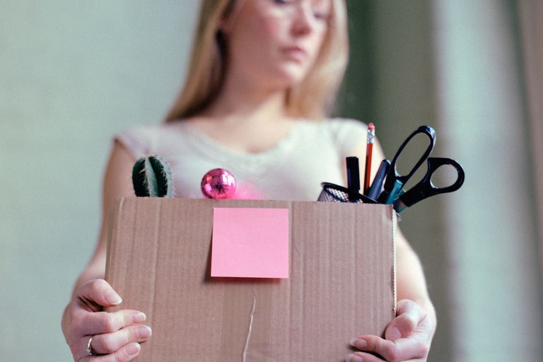 woman fired from job, carrying box of belongings