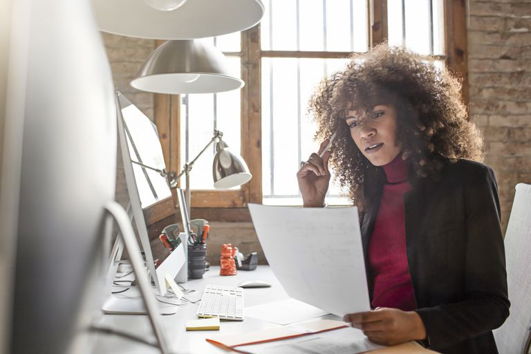Woman at computer looking at documents