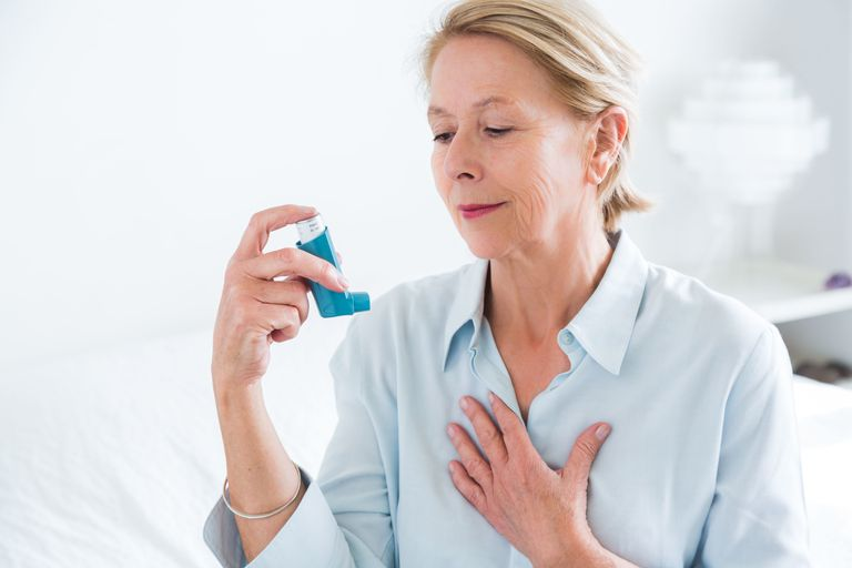 Woman using an aerosol inhaler to improve breathing.