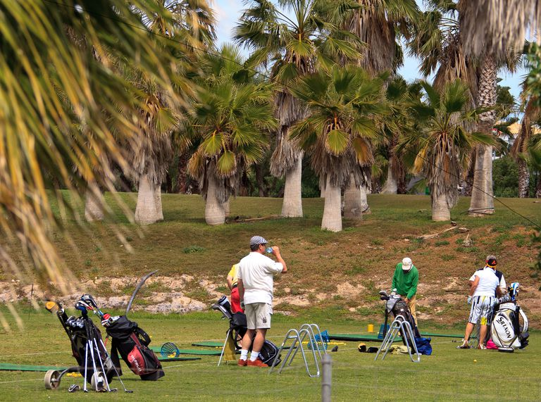 Golfers practise at the driving range of the palm fringed golf course Golf del Sur on March 25, 2011 in Tenerife, Spain