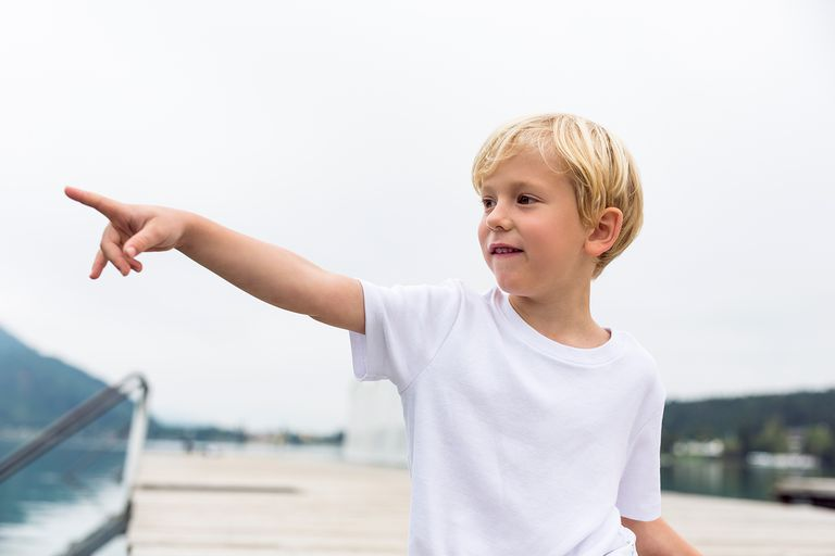 Portrait of little boy standing on a jetty pointing on something.