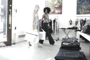 Two young women walking into clothing boutique