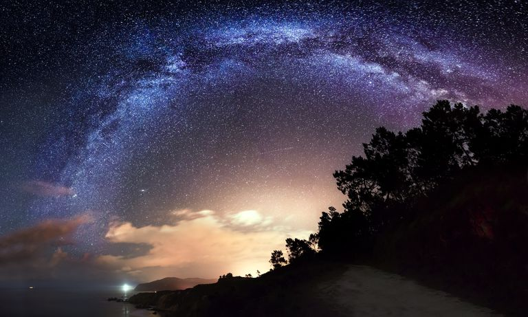 Milky Way arch over the sea and the trees in Galicia, Spain.