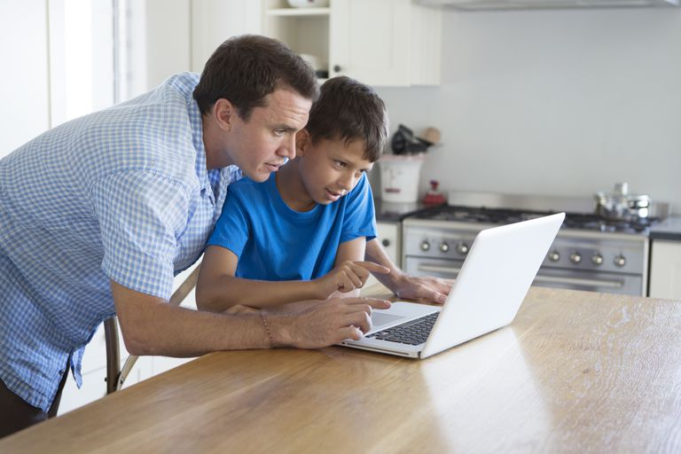 father and son using computer at home