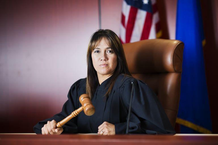 Female judge sitting in court holding her gavel