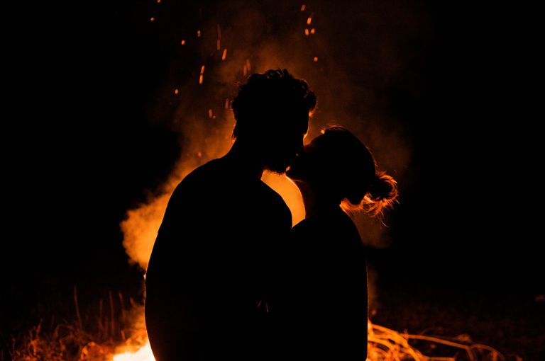 Silhouette of couple kissing by campfire