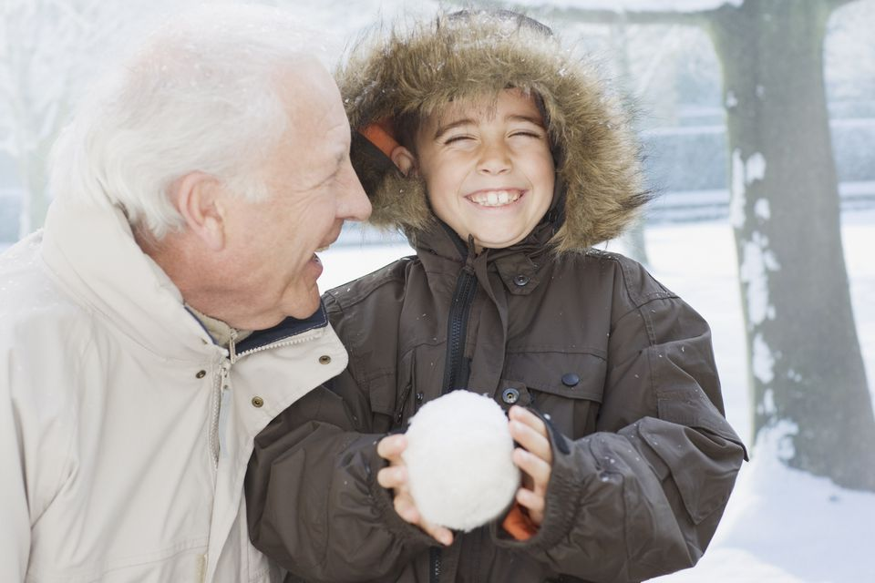 Grandfather and grandson holding snowball
