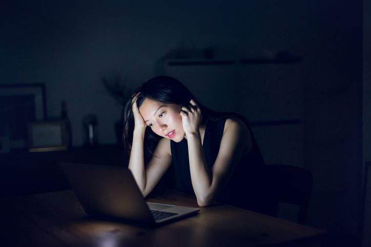 Woman sitting in front of laptop, illuminated by the glow of the screen