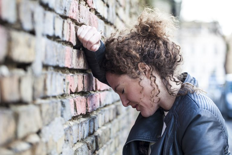 Woman leaning against brick wall
