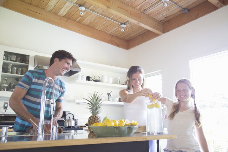 Family preparing lemonade in kitchen