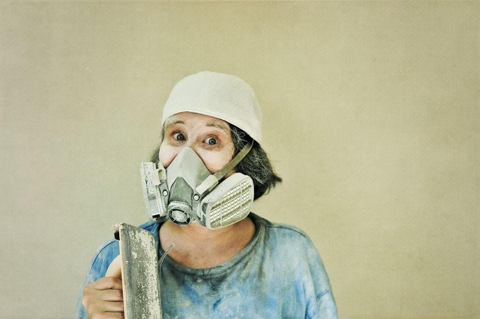 Woman with drywall sanding tool