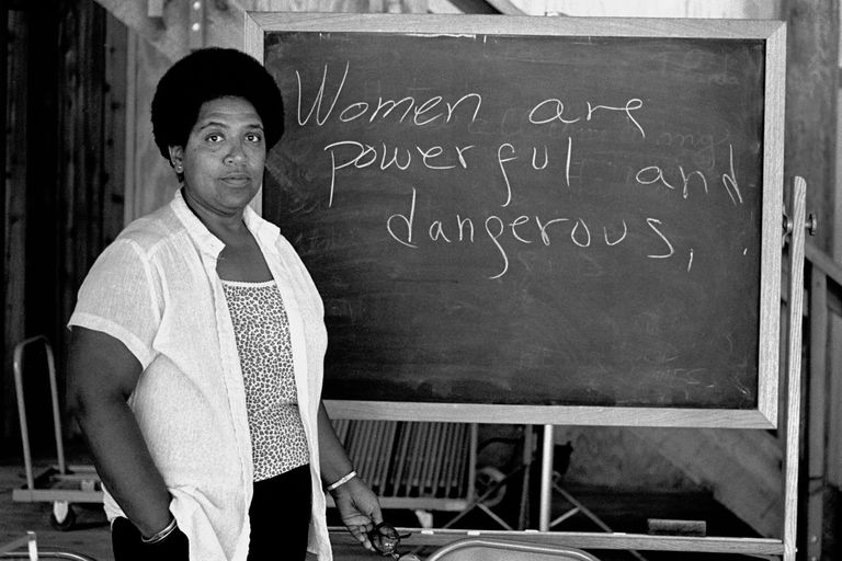 Audre Lorde lecturing, words on blackboard are Women are powerful and dangerous
