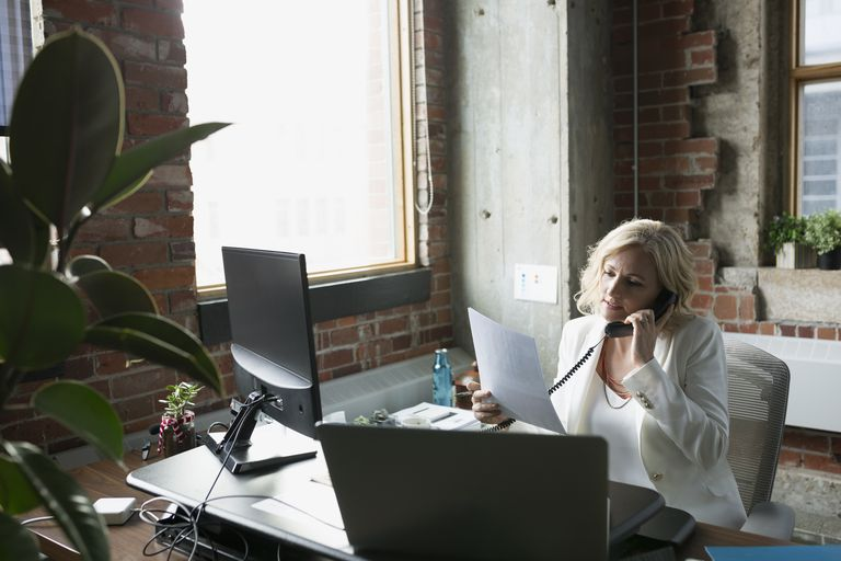 Businesswoman with paperwork talking on telephone in office