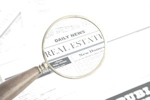 Close-up of real estate newspaper page seen through magnifying glass