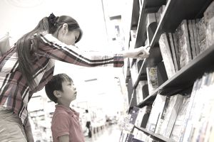 a mom and her son scanning the shelves in a bookstore