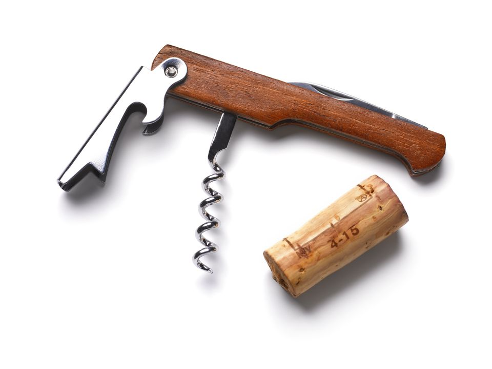 Cork screw and wine cork on white background