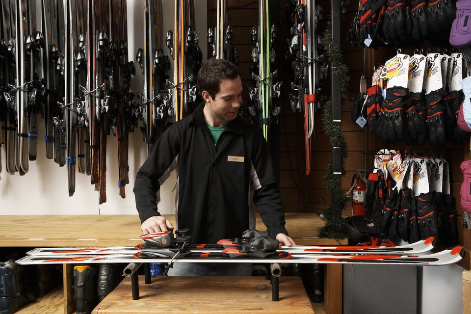Young man checking skis and bindings in sports shop