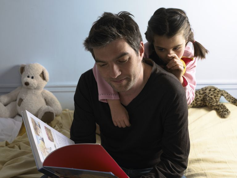 Father reading to daughter (5-7) sucking thumb resting arm on father