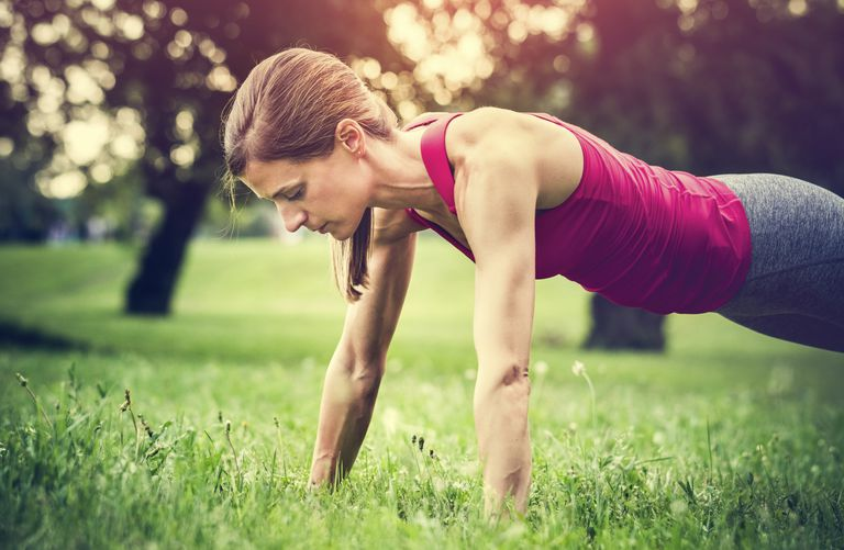 Woman doing push-up in the grass