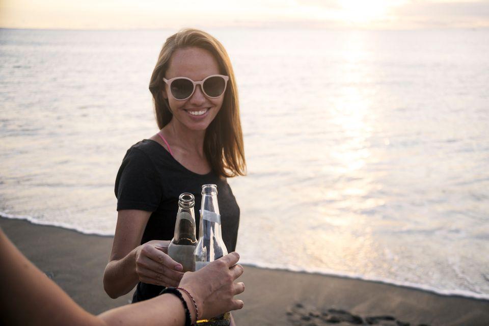 Bali tourist clinking beer bottles