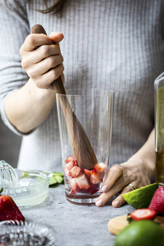 Woman muddling strawberries for margaritas.