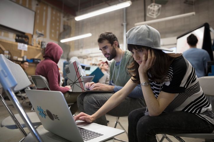 Focused female hacker wearing baseball cap working hackathon at laptop in workshop