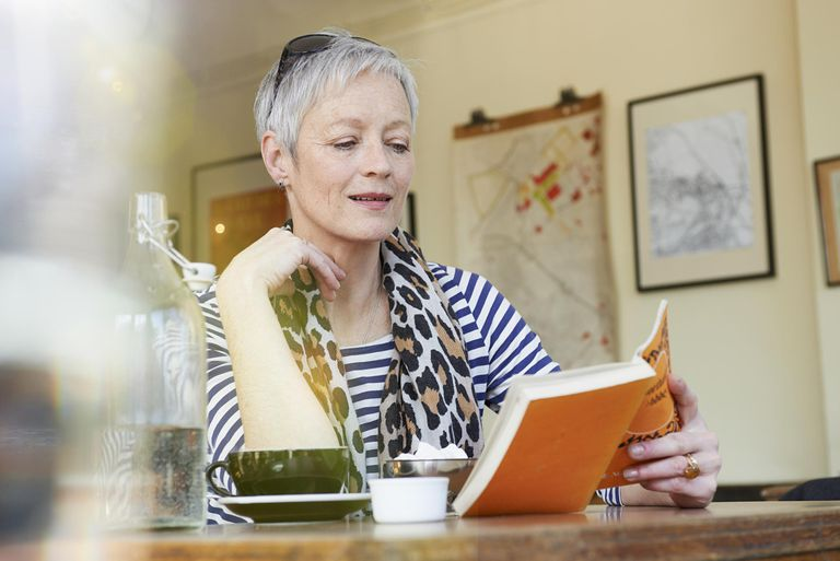 Mature woman reading book in cafe