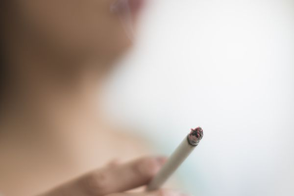 woman smoking cigarette which can cause heartburn
