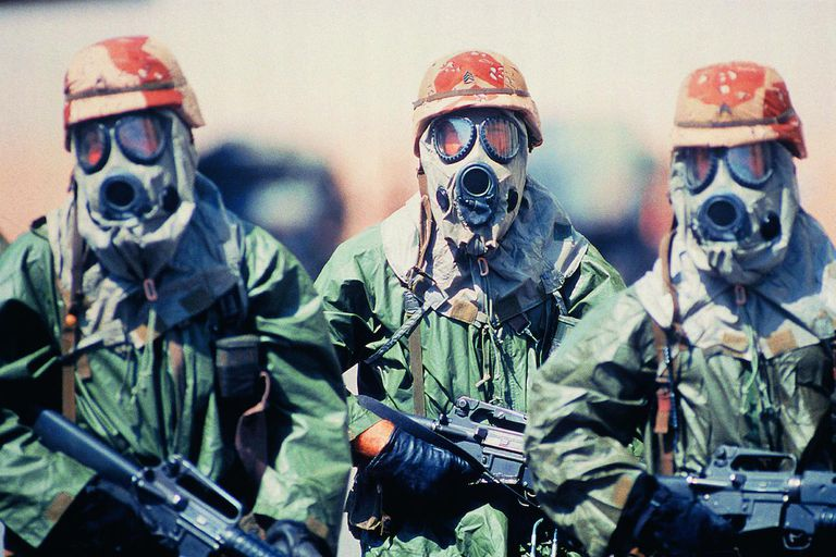 Troop of soldiers in camouflage uniforms, helmets and gas masks
