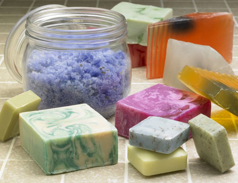 Fancy soaps and bath crystals on tile background