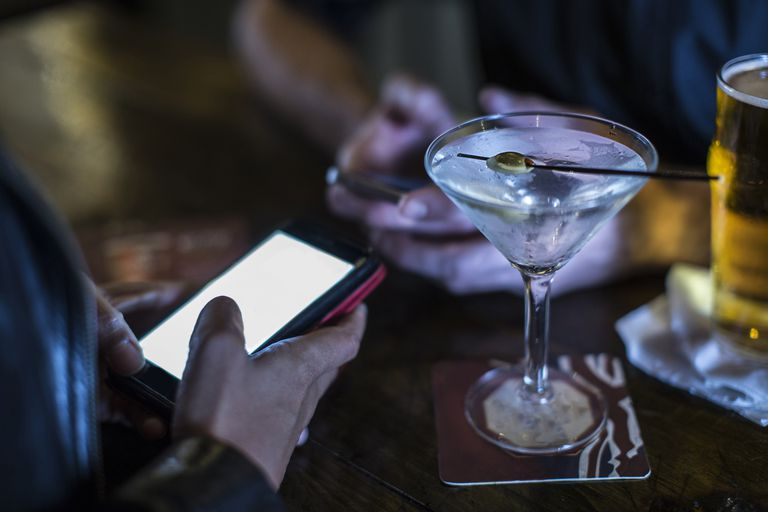 Close up of female hand using smartphone in public house