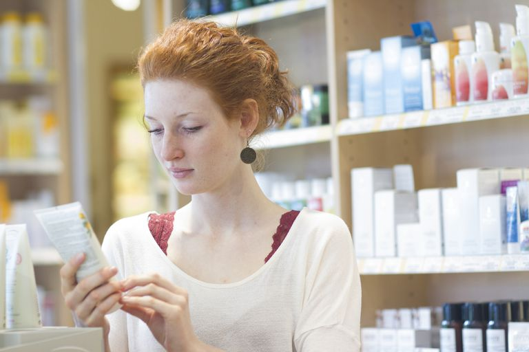 woman looking at bottle of product in store