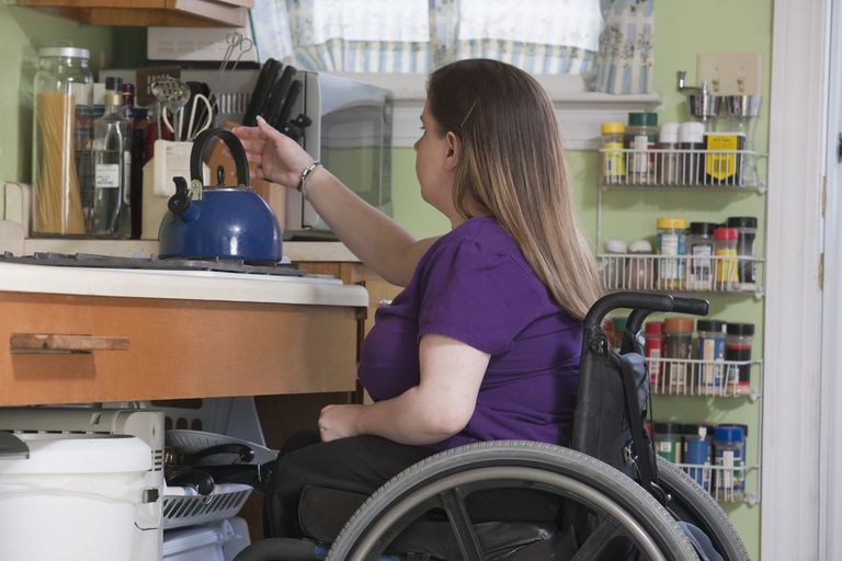 Woman in a wheelchair positioning a kettle in the accessible kitchen